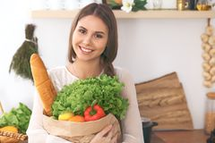 Young happy woman holding paper bag full of vegetables and fruits while smiling. Girl have made shopping and ready for Stock Images
