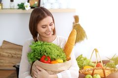 Young happy woman holding paper bag full of vegetables and fruits while smiling. Girl have made shopping and ready for royalty free stock photography