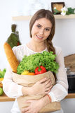 Young happy woman is holding paper bag full of vegetables and fruits while smiling in kitchen. Housewife have made Stock Image
