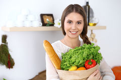 Young happy woman is holding paper bag full of vegetables and fruits while smiling in kitchen. Housewife have made Stock Photos