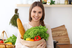 Young happy woman is holding paper bag full of vegetables and fruits while smiling in kitchen. Housewife have made Royalty Free Stock Photo