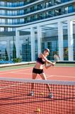 Young happy woman holding racket playing tennis Stock Photo