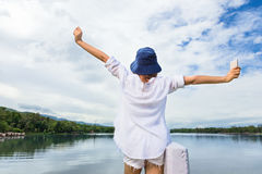 Young happy woman holding up her hands joyfully in front of a be Stock Photo