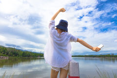 Young happy woman holding up her hands joyfully in front of a be Stock Image