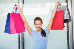 Young happy woman holding up her shopping bags Stock Images