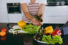 A young woman spends time at home, in the kitchen and in the roo. The young happy woman holding vegetables in hands in kitchen with laptop on the table Royalty Free Stock Photography