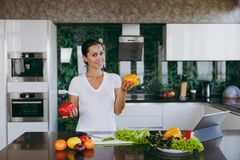 A young woman spends time at home, in the kitchen and in the roo. The young happy woman holding vegetables in hands in kitchen with laptop on the table Stock Photo