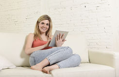 Young happy woman on home sofa using internet app on digital tablet pad Royalty Free Stock Image