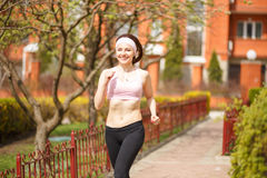 Young happy woman jogging along the street Royalty Free Stock Image
