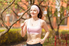 Young happy woman jogging along the street Stock Images