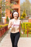 Young happy woman jogging along the street Royalty Free Stock Photo