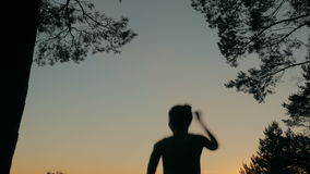 Young happy woman jumping, dancing and having fun in forest after sunset stock video