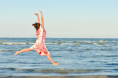 Young happy woman jumping high at seaside Stock Photography