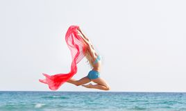 Young happy woman jumping with red scarf Royalty Free Stock Photo