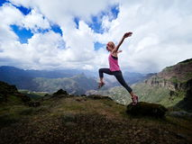 Young happy woman jumping on top of the mountain Royalty Free Stock Images