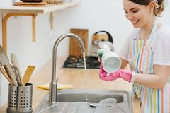 Young happy woman in a kitchen is washing cups and dishes royalty free stock photography