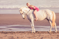 Young happy woman lies and hugs the horse Royalty Free Stock Photo