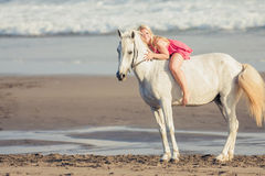 Young happy woman lies and hugs the horse Stock Photography