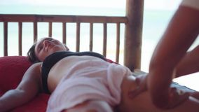 Young happy woman lies in spa saloon relaxing on the tropical beach. Massage therapist doing legs massage. Close up. Beautiful woman lies in spa saloon on the stock video