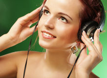 Young happy woman listening to music with headhones Royalty Free Stock Photos