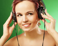 Young happy woman listening to music with headhones Royalty Free Stock Photography