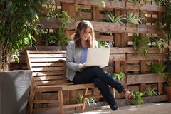 Young happy woman looking at laptop on the bench in the street w stock image