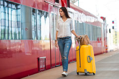 Young happy woman with luggage at a train station. Young woman with luggage on the platform waiting for aeroexpress Royalty Free Stock Photos