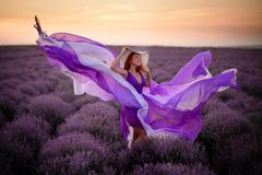 Young happy woman in luxurious purple dress standing in lavender field. At sunset