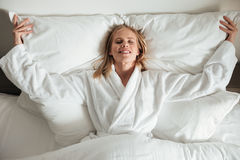 Young happy woman lying on big white bed Stock Images