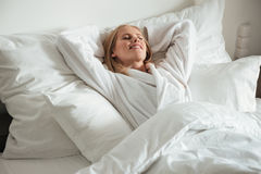 Young happy woman lying on big white bed Stock Photos