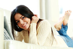 Young happy woman lying on the sofa Royalty Free Stock Image