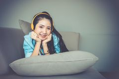 Young happy woman lying on sofa listening music with earphones. stock photos