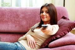 Young happy woman lying on the sofa with remote control Royalty Free Stock Photo