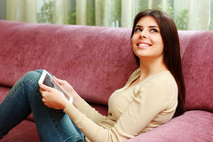 Young happy woman lying on the sofa with tablet computer and looking up Stock Images
