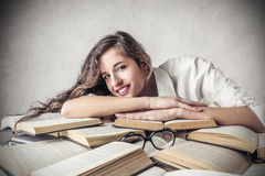 Young happy woman lying on some books. Young beautiful happy woman lying on some books while studying Royalty Free Stock Photography