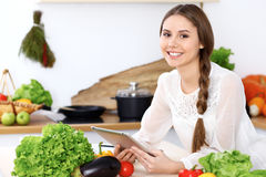 Young  happy woman is making online shopping by tablet computer while smiling. Housewife looking for a new recipe fo Royalty Free Stock Photography