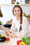 Young  happy woman is making online shopping by tablet computer while smiling. Housewife looking for a new recipe fo Royalty Free Stock Photo
