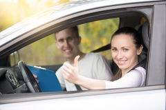 Young happy woman and man in the car. Lifestyle portrait of young happy confident lady have just finished drivers education class, showing thumb up, experienced stock photography