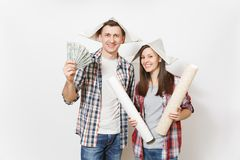 Young happy woman, man in casual clothes holding bundle of dollars, cash money and wallpaper roll. Couple isolated on stock photo