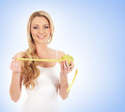A young and happy woman measuring an apple Stock Images