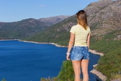 Girl enjoying the lake. Young happy woman at the mountain, relaxing and enjoying the lake at Geres, Portuguese National Park royalty free stock photography