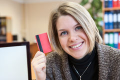 Young happy woman paying by plastic card Stock Image