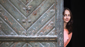 Young happy woman peeks out from behind big ancient doors. Stock Images