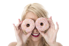 Young Happy Woman Playing with Two Iced Donuts Over Eyes Stock Photo