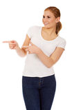 Young happy woman pointing for copyspace or something Royalty Free Stock Photo
