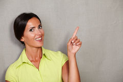 Young happy woman while pointing upward Stock Image