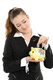Young happy woman putting money in the piggybank Royalty Free Stock Photo
