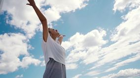 Young happy woman raises hands in background of white clouds and bright blue sky stock video