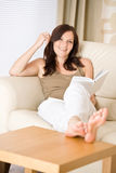 Young happy woman read book on sofa Royalty Free Stock Image