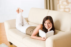 Young happy woman read book on sofa Stock Images